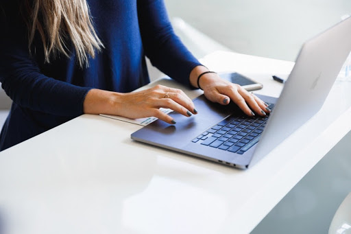 women with blue nails using macbook